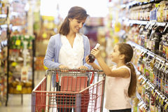 Mother and daughter shopping in supermarket royalty free stock photography