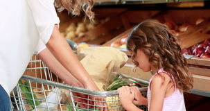 Mother and daughter shopping in supermarket stock video