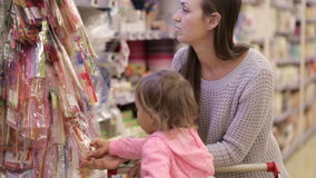 Mother and daughter shopping in supermarket. Mom and girl choosing goods for celebrate stock video