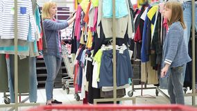 Mother and daughter shopping trip. Beautiful caucasian family - mother and daughter in a clothing store. Woman with her little child having fun together during stock video
