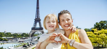Mother and daughter showing heart shaped hands in Paris, France Stock Photo