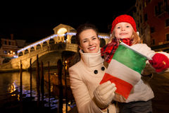 Mother and daughter showing Italian flag in Christmas Venice Royalty Free Stock Image