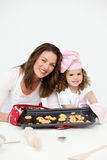 Mother and daughter showing a plate with biscuits Royalty Free Stock Photography