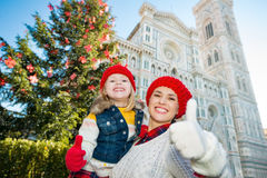 Mother and daughter showing thumbs up in Christmas Florence. Smiling mother and daughter showing thumbs up in front of Christmas tree near Duomo in Florence stock images