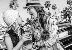Mother and daughter showing tongues after drinking cocktail. Summertime at colorful Barcelona. happy stylish mother and daughter tourists on embankment in Royalty Free Stock Photography