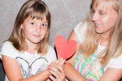 Mother and daughter shows heart. Mother and daughter with heart in hands Stock Photo