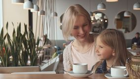 Mother and daughter shows their thumbs up at the cafe royalty free stock photos
