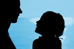Mother with daughter silhouette near sea Stock Photos