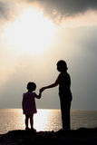 Mother and Daughter Silhouettes. A mother and daughter stand silhouetted, holding hands as they watch the sunset from a sandy beach overlooking the ocean Royalty Free Stock Photo