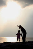 Mother and Daughter Silhouettes. A mother stands with her daughter and points to the setting sun as they stand silhouetted on a sandy beach overlooking the ocean Stock Image