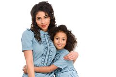 Mother and daughter in similar dresses embracing and looking at camera. Isolated on white stock photography