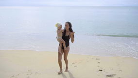 Mother and daughter are singing and dancing on the beach stock footage