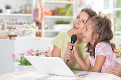 Portrait of mother and daughter singing karaoke with microphone together royalty free stock photo