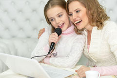 Mother and daughter singing karaoke Stock Photo