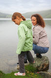 Mother with daughter sit at background of lake Stock Photos