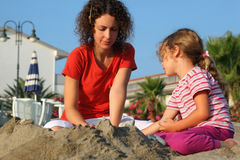Mother with daughter sit on beach and play Royalty Free Stock Photos
