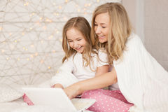 Mother and daughter sit on bed in pajamas and have fun, use laptop. Lifestyle. Happy family. Education, learn. Pastel stock photo