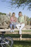 Mother And Daughter Sit On Fence Looking At Map Royalty Free Stock Images
