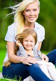 Mother and daughter sit on the grass Royalty Free Stock Images