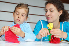 Mother and daughter sit and make artificial flower Stock Photography