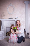 Mother and daughter sit near the fireplace Royalty Free Stock Photography