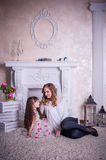 Mother and daughter sit near the fireplace Royalty Free Stock Photos