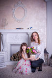 Mother and daughter sit near the fireplace Stock Image