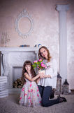 Mother and daughter sit near the fireplace Stock Photos