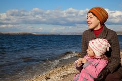 Mother and daughter sit near lake and look Stock Images