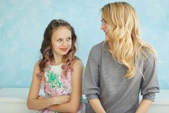 Mother and daughter sit next to each other and writhe faces royalty free stock images