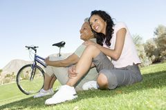 Mother And Daughter Sit In Park With Mountain Bike Stock Photos