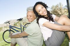 Mother And Daughter Sit In Park With Mountain Bike Stock Images