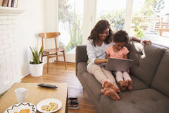 Mother And Daughter Sit On Sofa At Home Using Laptop royalty free stock photography