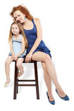 Mother and daughter sit on stool Stock Image