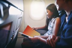 Mother with daughter sit on their place in airplane stock images