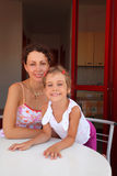 Mother with daughter sit on verandah near table Royalty Free Stock Images
