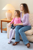 Mother and daughter sits on couch in cozy room Stock Photos