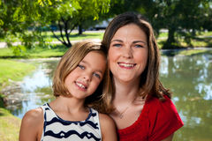Mother Daughter. A daughter sits on her mother's lap in front of a pond for a portrait Royalty Free Stock Image