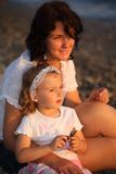 Mother with daughter sits on seacoast Royalty Free Stock Image