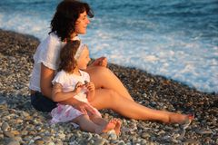 Mother with daughter sits on seacoast Stock Image