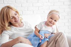 Mother with daughter sitting in armchair on white wall background. Mother with daughter sitting in armchair on white brick wall background Royalty Free Stock Photography