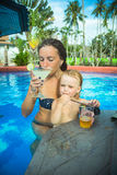 Mother with daughter sitting in bar and drinking Stock Photography