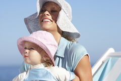 Mother and daughter (2-3) sitting on beach in deckchair, wearing sun hats, smiling, close-up stock photos