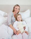 Mother and daughter sitting on bed Royalty Free Stock Photos