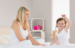 Mother and daughter sitting on bed at home Stock Images