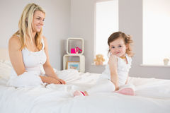 Mother and daughter sitting on bed at home Royalty Free Stock Photography