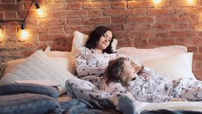 Mother and daughter are sitting on bed in pajamas and watching tv together.Family time stock video