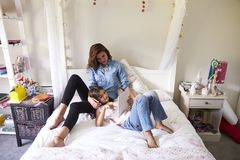Mother And Daughter Sitting On Bed Using Digital Tablet Royalty Free Stock Photos