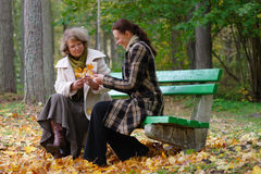 Mother and daughter sitting on a bench stock photos