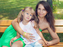 Mother and daughter. Sitting on a bench in the park royalty free stock image